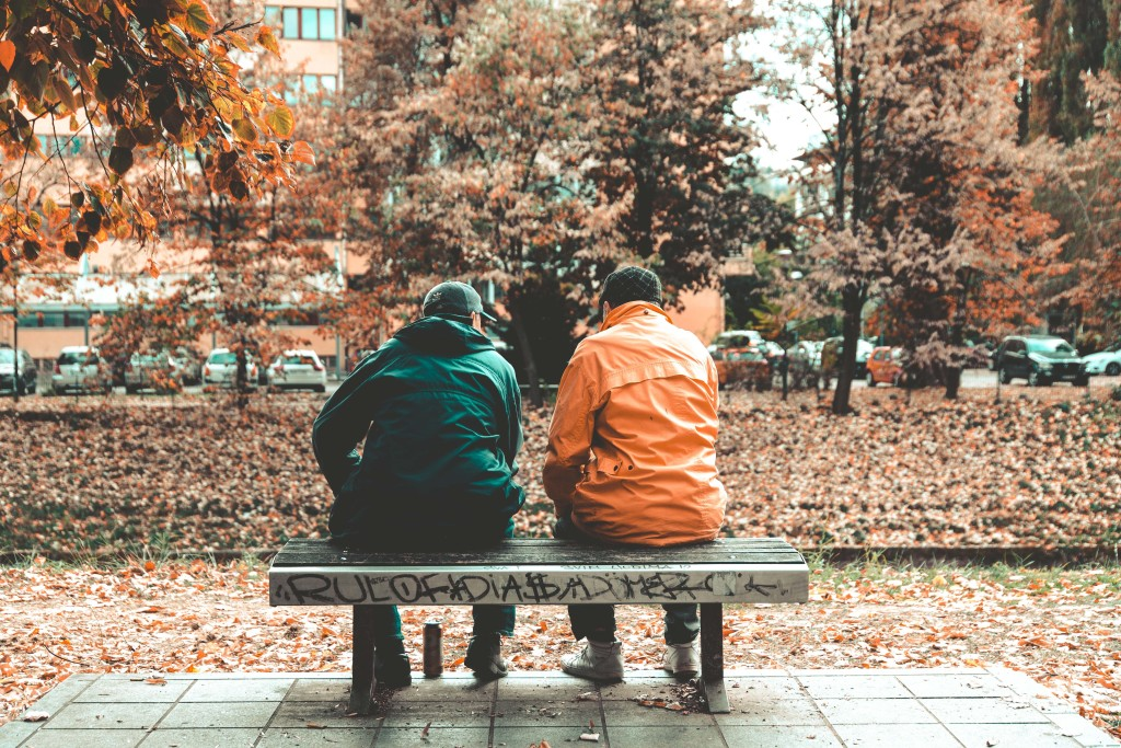Photo of two people sitting with their backs to the camera on a park bench. The people are wearing rain jackets. The park bench has graffiti on it. The leaves on the trees have turned orange. The ground is covered with fallen leaves.